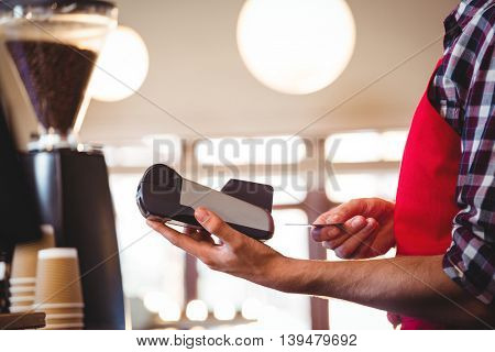 Mid section of waiter inserting customer's credit card into credit card machine