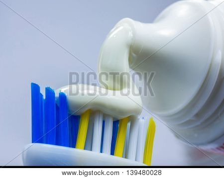 toothpaste out of the tube lies on a toothbrush