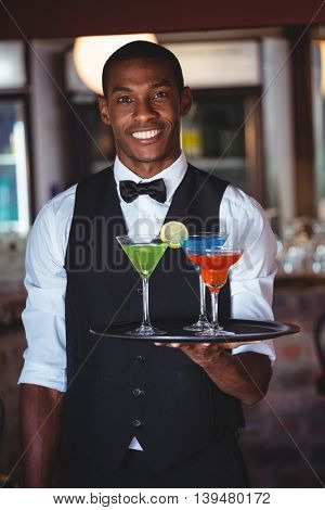 Portrait of smiling bartender holding serving tray with cocktail glasses
