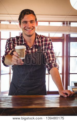 Portrait of smiling waiter offering a cup of coffee