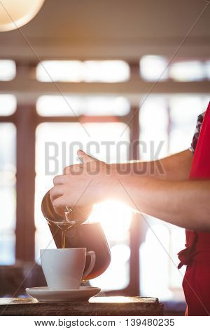 Mid section of waiter pouring a cup of coffee on counter