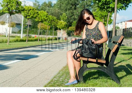 Girl Sitting On Bench In Park Opening Backpack