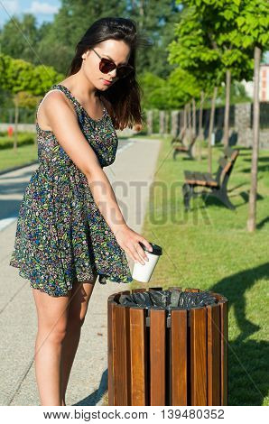 Beautiful Girl Throwing Paper Cup On Trash In Park