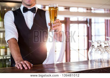 Mid section of bartender standing at bar counter offering a glass of beer