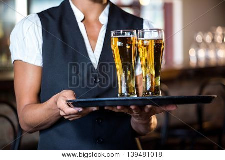 Mid section of waitress holding serving tray with two glass of beer