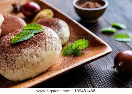 Traditional sweet steamed dumplings with a plum jam, sprinkled with cocoa powder on a wooden plate and background