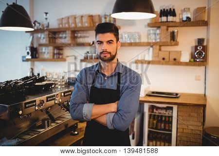 Portrait of man standing with arms crossed in office cafeteria