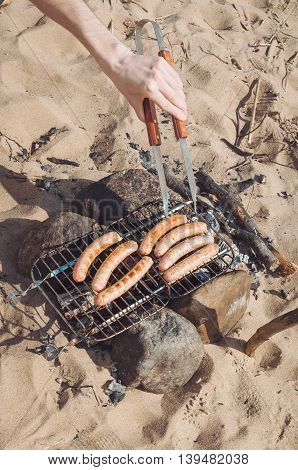Grilled sausages on the barbecue rack outdoor food items set. Delicious frankfurters on grill. Picnic rest cooking gear on the nature. Summer BBQ and grill tools. Campfire coal and rope on sandy beach. The concept of eating outdoors in the weekend.
