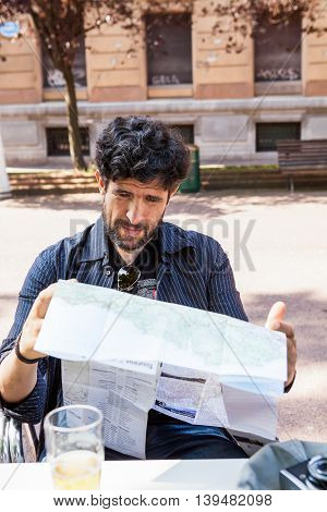 Traveler middle-aged hipster consulting a map resting on a summer terrace in the city