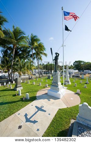KEY WEST FLORIDA USA - MAY 02 2016: Statue and American flag at the middle of the battleship Maine memorial section at the Key West cemetery.
