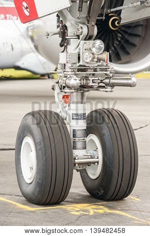 FARNBOROUGH, UK - JULY 15: Closeup section of an Airbus A350 nose wheel undercarriage on the taxiway at an aviation event in Farnborough, UK on July 15, 2016