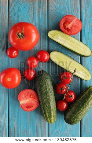 Composition of vegetables on blue wooden desk. Tomatoes, cucumber. Top view.