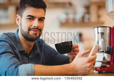 Portrait of young man holding mobile phone and coffee cup in office cafeteria