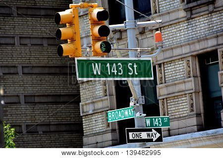 New York City - June 2 2016: Traffic light and street signs at Broadway and West 143rd Street in Hamilton Heights