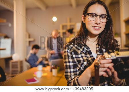 Portrait of graphic designer holding pictures in camera in office
