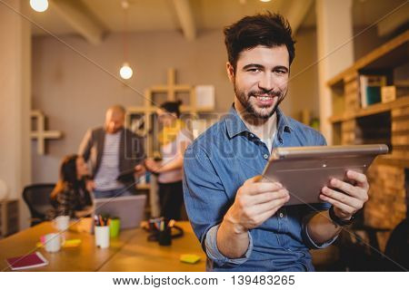 Portrait of graphic designer holding digital tablet while colleagues interacting in background