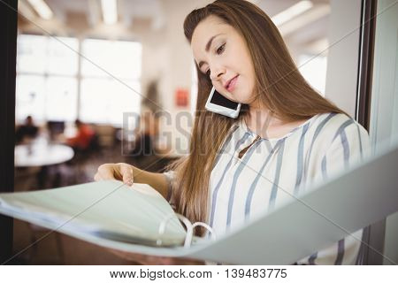 Young businesswoman looking at files while using mobile phone in office cafeteria