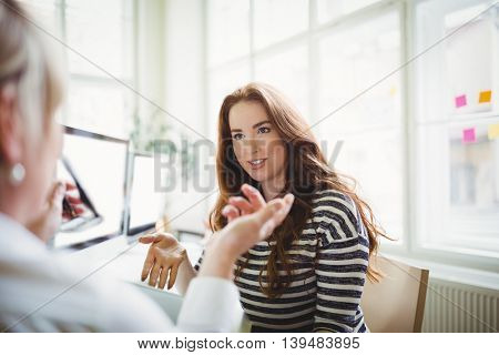 Young businesswoman discussing with female colleague in creative office