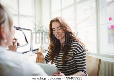 Young businesswoman using laptop while discussing with female colleague in creative office