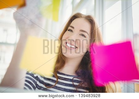 Smiling young businesswoman touching adhesive notes on window in creative office