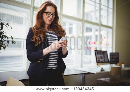 Young businesswoman using phone at creative office