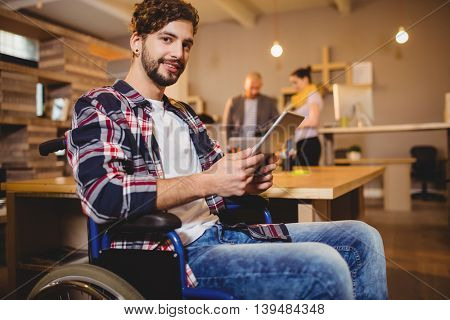 Portrait of graphic designer using digital tablet while colleagues interacting in background