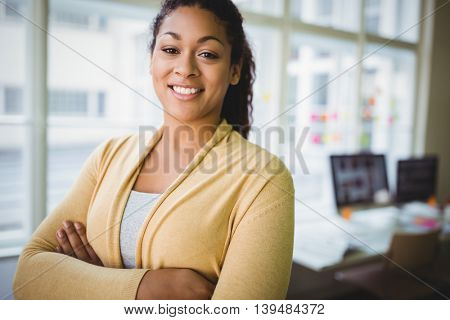 Portrait of confident young businesswoman with arms crossed in creative office