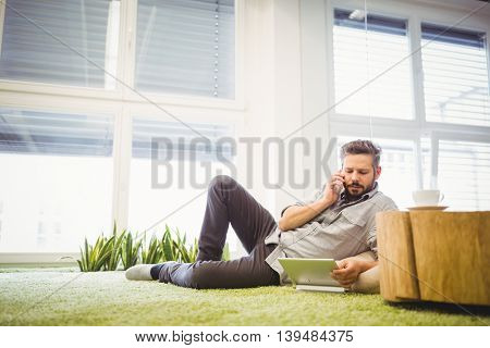 Young businessman talking on phone while using laptop at creative office