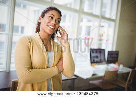 Smiling businesswoman using mobile phone at creative office