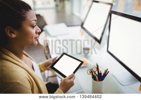 Young businesswoman looking at computer while using digital tablet in creative office