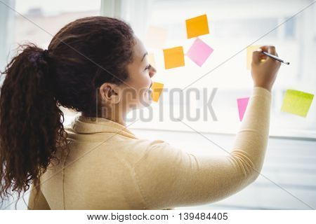 Rear view of businesswoman writing on adhesive notes in creative office