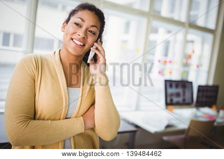 Businesswoman smiling while using mobile phone at creative office