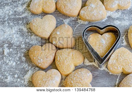 Heart shaped cookies powdered with flour and sugar