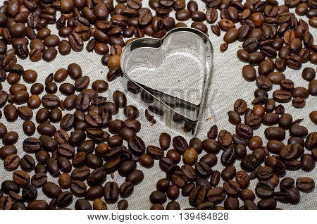 Heart shaped pastry cutters and coffee beans as background