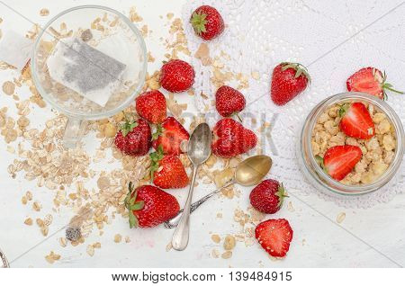 Ripe and tasty strawberries and tea with scattered muesli on white background