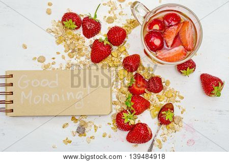 Good morning note in a notebook with craft brown pages ripe strawberries berry tea and oat muesli for breakfast