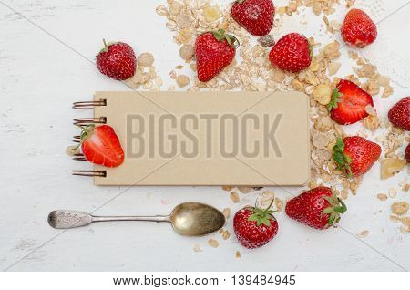 Blank craft notebook with ripe strawberries and muesli on white background