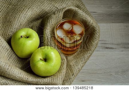 Glass of apple juice with ice on background of sackcloth with a green apple on the side. Healthy and organic food.