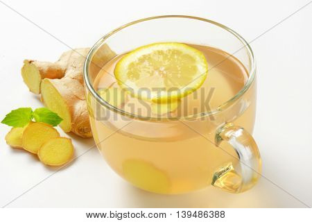 close up of cup of ginger tea with lemon and fresh ginger on white background