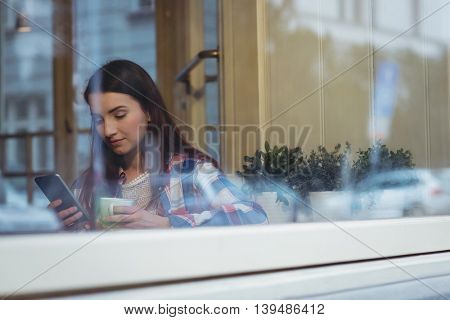Beautiful young woman using mobile phone at cafe
