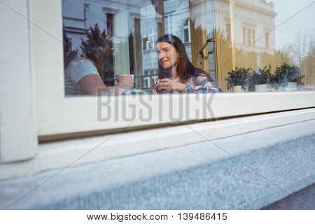 Young female friends talking at cafe