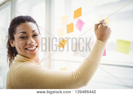 Portrait of happy businesswoman writing on adhesive notes in creative office