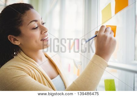 Businesswoman smiling while writing on adhesive notes in creative office