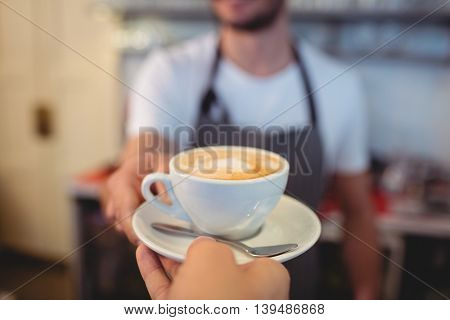 Cropped image of male customer taking coffee from waiter at cafe