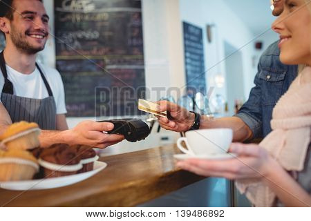 Happy young customers and male barista at coffee shop