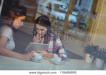Young beautiful women looking at tablet computer in coffee house