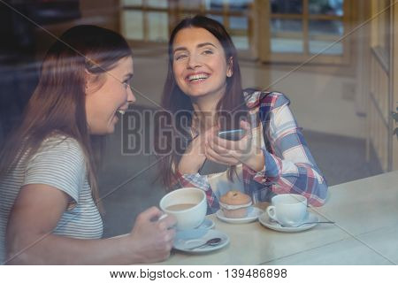 Cheerful young women with cellphone at coffee shop