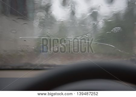 Inside the car. Driving on the road during the rain.