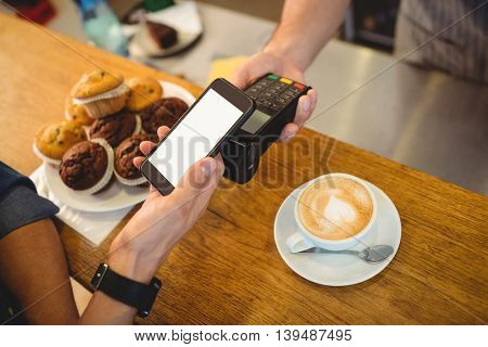 High angle view of customer and male barista with technologies at cafe