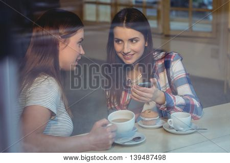 Happy young female friends using cellphone at cafe